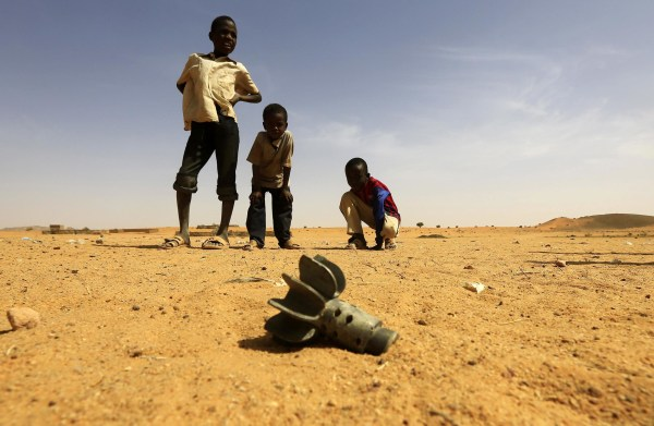 Image: Children look at the fin of a mortar projectile that was found at the Al-Abassi camp for internally displaced persons, after an attack by rebels, in Mellit town