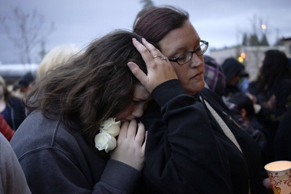 Image: Sarah Halstead comforts her daughter Allison at a candlelight vigil for mudslide victims in Arlington