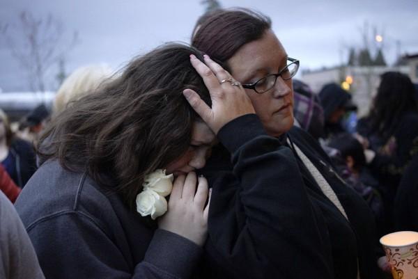 Image: Sarah Halstead comforts her daughter Allison at a candlelight vigil for mudslide victims in Arlington