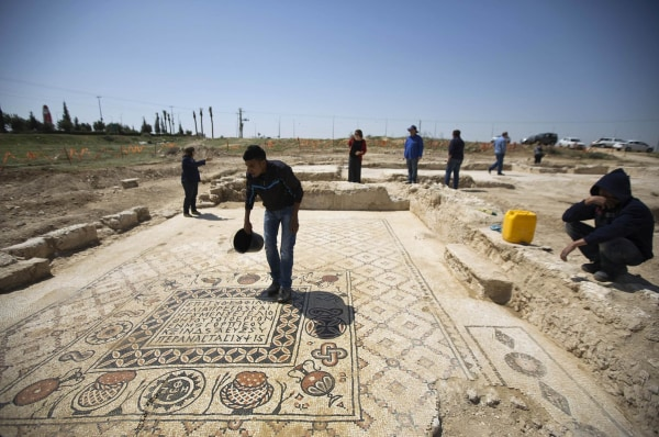 Image: A worker for the Israel Antiquities Authority (IAA) stands on the mosaic floor of a monastery unearthed during excavations in Hura, east of Beersheba