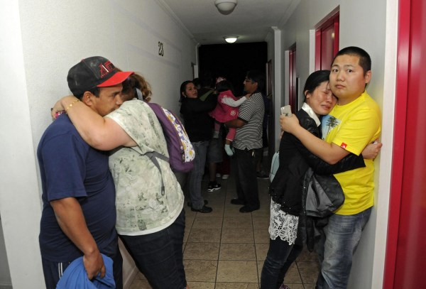 Image: People embrace on the upper floor of an apartment building located a few blocks from the coast where they gathered to avoid a possible tsunami