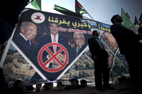 Image: Palestinian protesters stand in front of a giant banner showing Secretary of State John Kerry