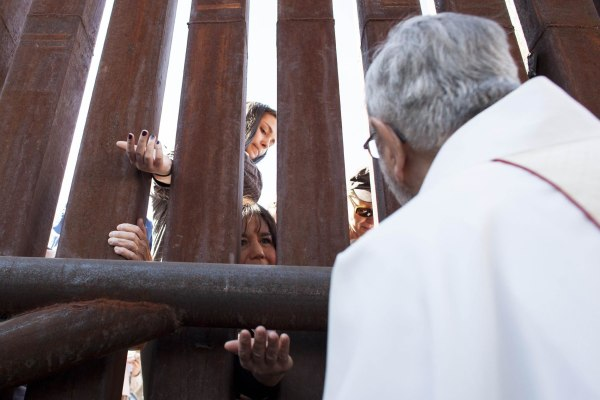 Image: Tucson Diocese Bishop Kicanas offers Holy Communion through the border to the Mexico side of the fence, during a special mass at the United States and Mexico border near Nogales