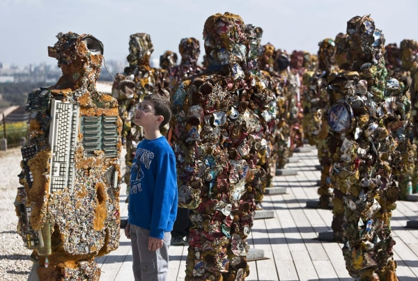 Image: A boy looks at a statue by German artist HA Schult during a preview of the artist's exhibition at the Ariel Sharon Park near Tel Aviv
