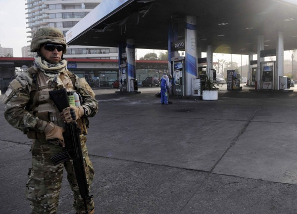 Image: A soldier guards a gasoline station after a tsunami hit the northern port of Iquique
