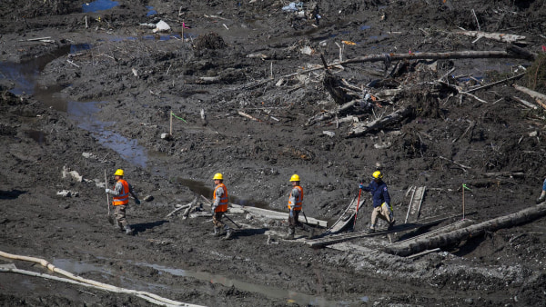 Image: Workers cross the site of the mudslide near Oso, Wash., where 27 are now confirmed to have died.