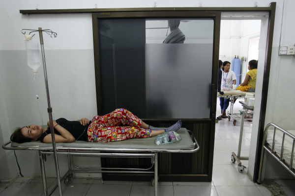 A garment worker recovers at a hospital after fainting at a factory in Phnom Penh April 3, 2014.