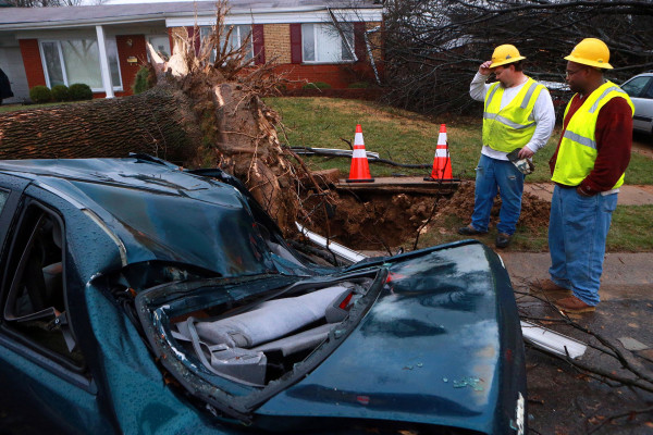 Image: Jason Reidl, left, and Chris Thomas with Laclede Gas, look at a fallen tree that ruptured a gas main in University City, Mo.