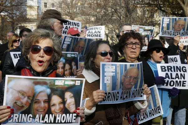 Image: Supporters of Alan Gross, seen on posters, hold an event to mark his fourth year in prison in Cuba