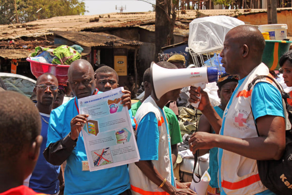 Image: Health workers teach people about the Ebola virus in Guinea