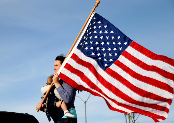Image: Mellissa Phillips holds Sierra Phillips as she and others participate in a flag walk in memory of those killed and injured by Iraq war veteran, Ivan Lopez, in Killeen, Texas