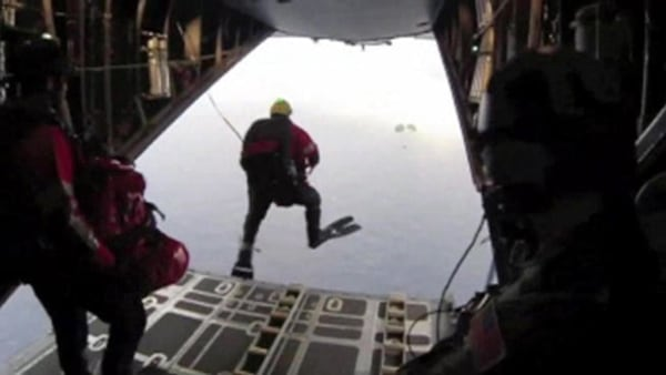 Image: Four pararescuers jump out of an airplane to rescue a child on sailboat