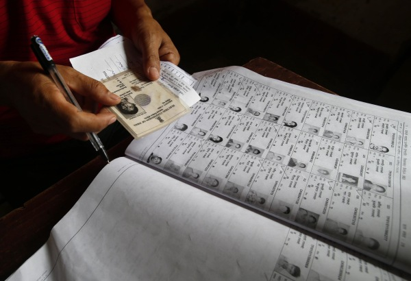Image: Election official checks voter's identity in Agartala, India
