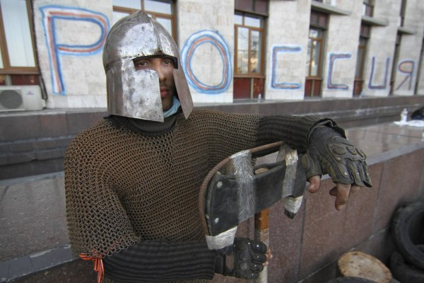 Image: A man is seen wearing medieval armour as pro-Russian protesters gather outside a regional government building in Donetsk