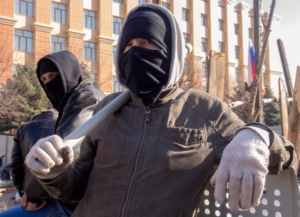 Image: Pro-Russian activists in face masks stand near a barricade in front of an entrance of the Ukrainian regional office of the Security Service in Luhansk