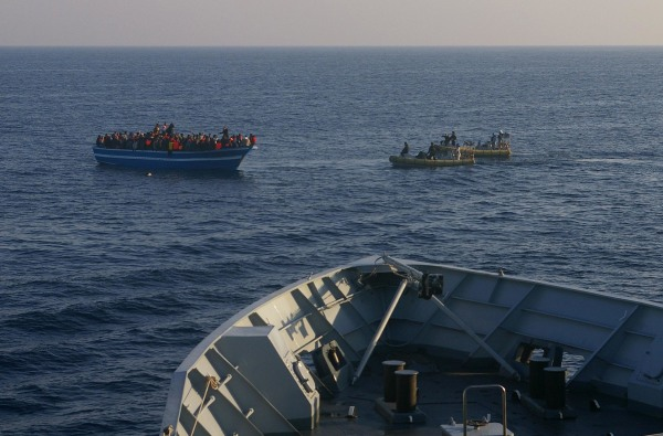 Image: Italian Navy dinghies approach a boat carrying migrants off the Sicilian island of Lampedusa
