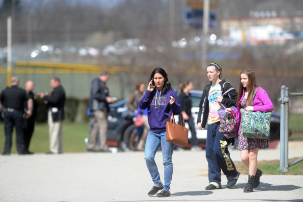 Image: Parents and children are reunited at an organized pickup for parents at the Elementary School following a stabbing spree at Franklin Regional Senior High School