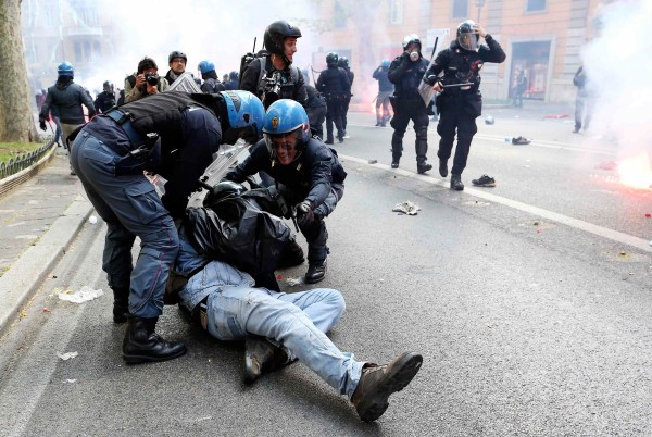 Image: A demonstrator is detained by policemen during a protest in downtown Rome