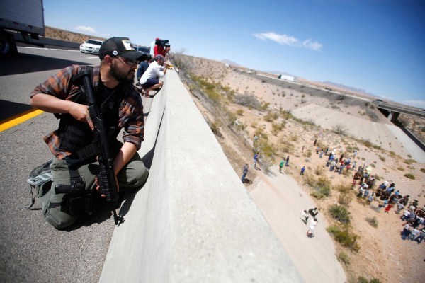 Image: An armed man stands watch as protesters gather by the Bureau of Land Management's base camp near Bunkerville, Nevada