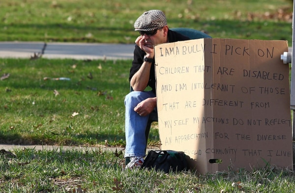 """Image: Aviv sits with an """"I am a bully"""" sign at a street corner in the Cleveland suburb of South Euclid"""