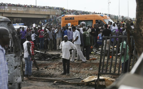 Image: Crowd gather at the scene of a bomb blast at a bus terminal in Nyayan, Abuja