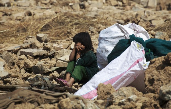 Image: An Afghan refugee girl sits with her belongings after authorities razed her house in the slums of Islamabad