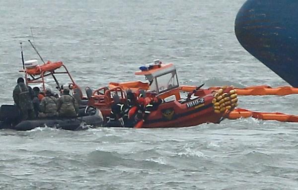 Image: South Korean Coast Guard rescue teams retrieve the body of a dead passenger