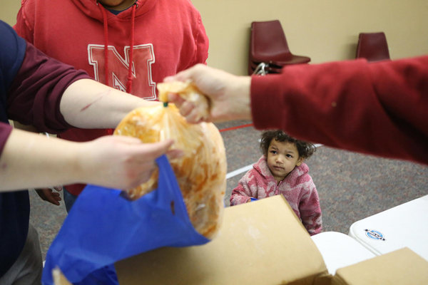 Image: Olivia Grimes, 3, watches a food line volunteer hand a turkey to her mother Jaime in Lincoln, Nebraska.