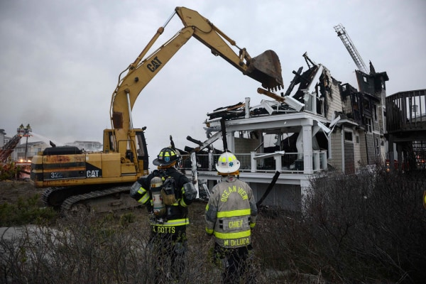 Image: Firefighters tear through a beachfront home which caught fire in Sea Isle City, New Jersey