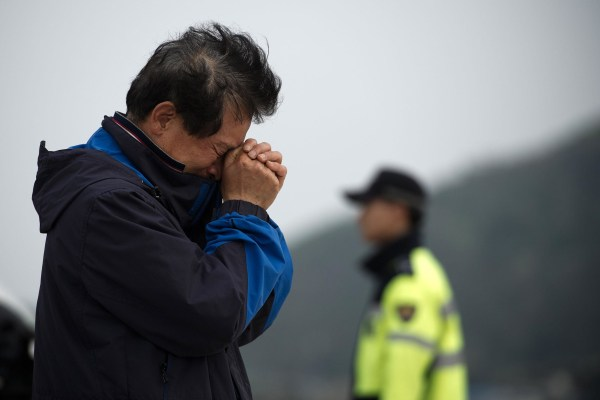Image: A relative weeps at an area where family members of victims of the South Korean ferry 'Sewol' are gathered