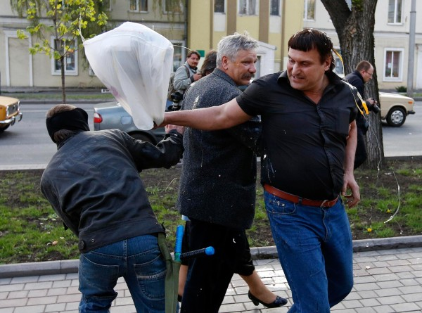 Image: A masked pro-Russia protester pelts supporters of Yulia Tymoshenko with eggs outside a regional government building in Donetsk