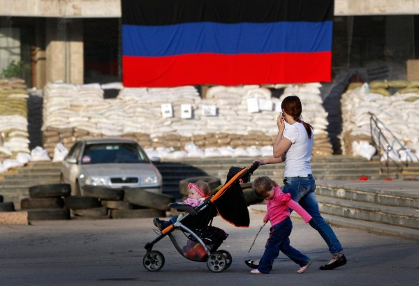 Image: A woman with children passes by barricades in Slaviansk