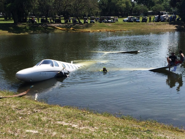 Image: Workers begin to remove the Cessna 525 from the water after it rolled into a Florida pond on Saturday.