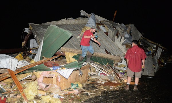 Image: Business owners look over damage after a tornado hit the town of Mayflower, Ark.