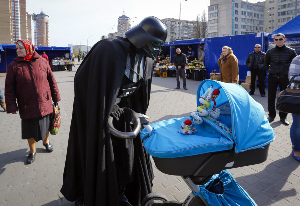 "Image: ""Darth Vader"", the leader of the Internet Party of Ukraine, looks at a child in a pram at a street market near the Ukrainian Central Elections Commission in Kiev"