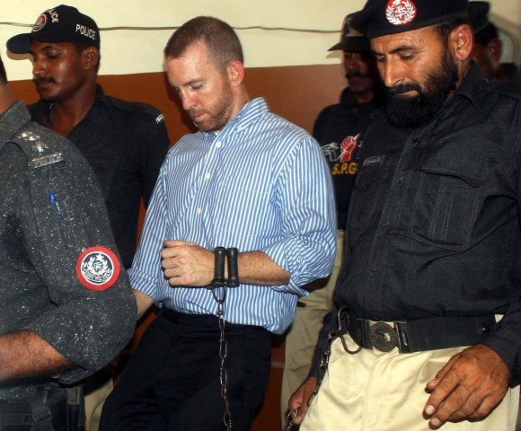 Image: Pakistani policemen escort a man said to be an FBI agent as they leave a court in Karachi