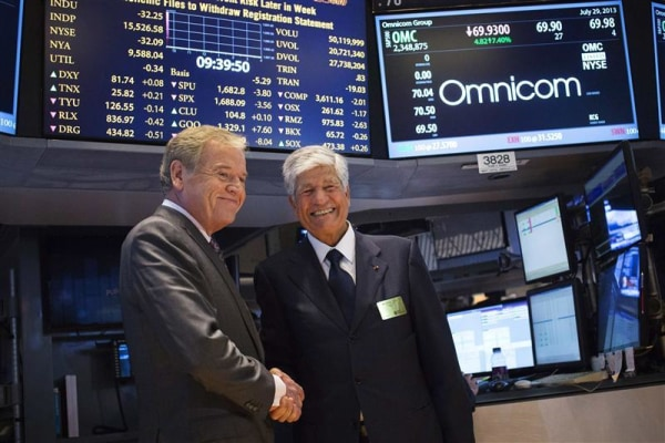 Omnicom Chief Executive Wren and Publicis Group Chairman and CEO Levy shake hands after announcing an agreement on their merger on the floor of the New York Stock Exchange