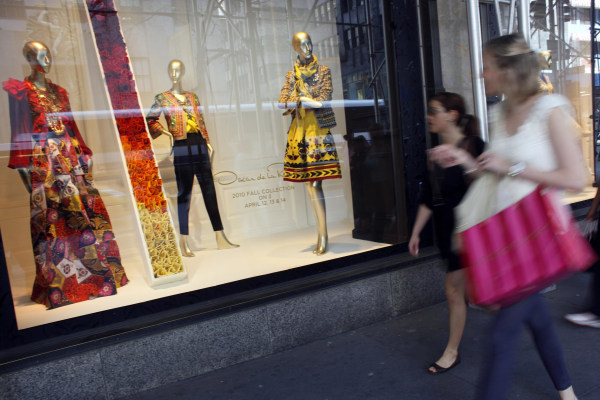 Image: Shoppers walk past the the Oscar de la Renta display at the Saks 5th Ave. retail store