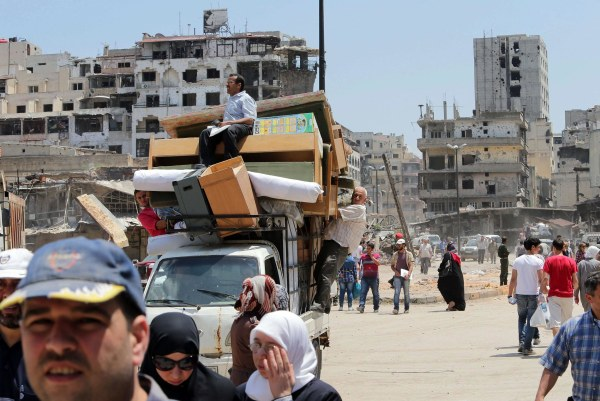 Image: Residents of the Old City of Homs ferry items out from their destroyed neighborhood on May 12