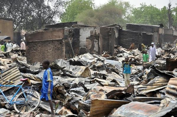 Image: A boy walks past burnt shops at Ngumborum central Market, on May 11