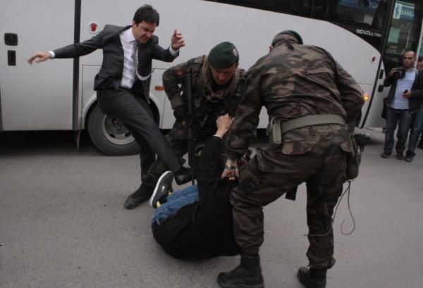 Image: A protester is kicked by Yusuf Yerkel, advisor to Turkey's Prime Minister Tayyip Erdogan, as Special Forces police officers detain him during a protest against Erdogan's visit to Soma