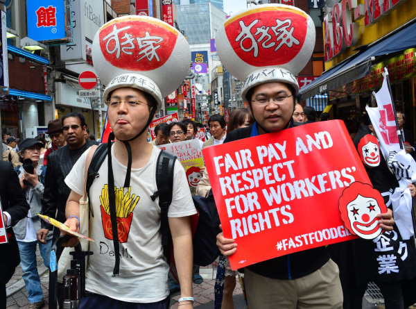 Labor union members wearing gear of Sukiya fast-food beef-bowl restaurant hold placards to demand payment of 1,500 yen (15 USD) an hour for part-time jobs during a march in Tokyo on May 15, 2014.
