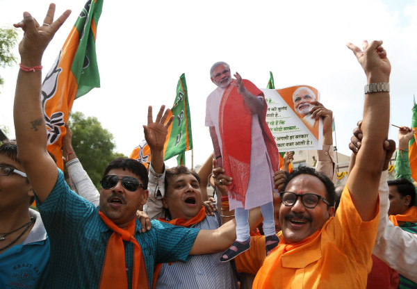 Image: Indian supporters celebrate by dancing and distributing sweets at the Bharatiya Janata Party's state headquarter in Gandhinagar.