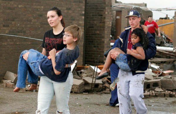 Image: Teachers carry children away from Briarwood Elementary school after a tornado