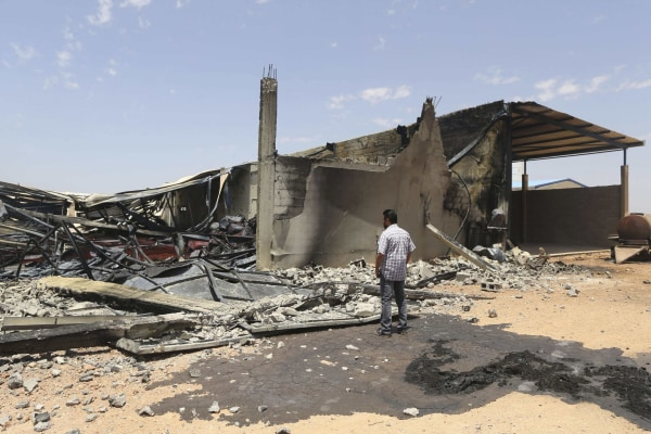 Image: A man looks at destroyed warehouses following Friday's clashes between Libyan irregular forces and Islamist militias in Benghazi