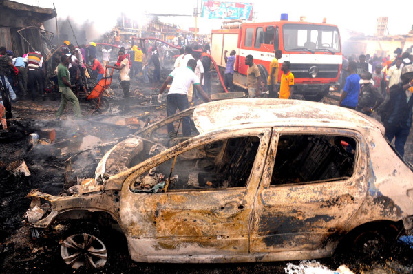 Image: Firefighters and rescuers extinguish a fire at the scene of a bomb blast at Terminus market in the central city of Jos