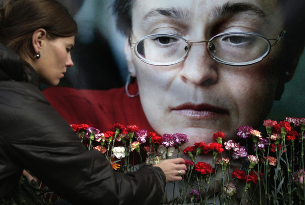 Image: A woman places flowers before a portrait of slain Russian journalist Anna Politkovskaya
