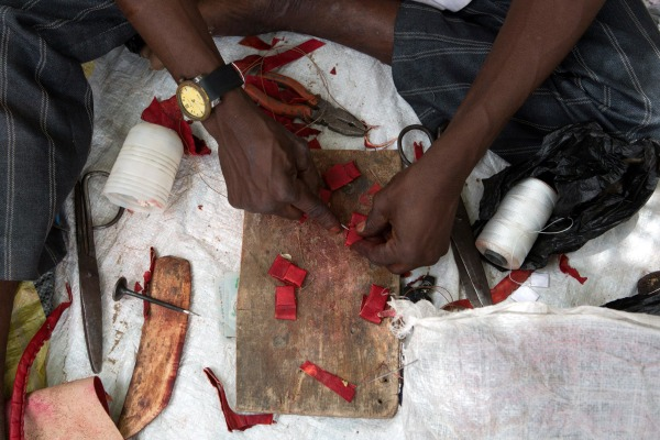 Image: A man makes charms at a camp of a vigilante group of traditional hunters in Maiduguri