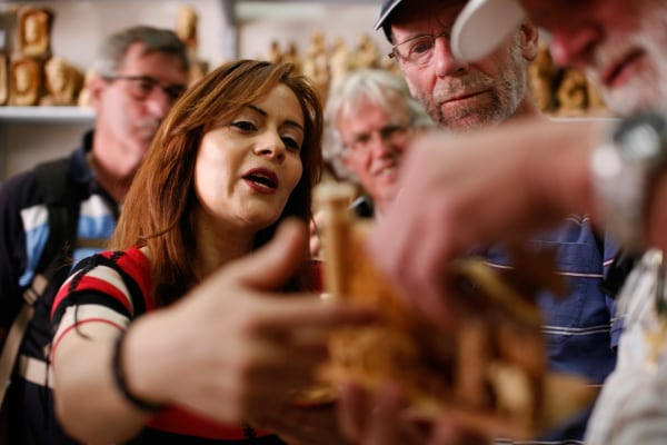 Claire Anastas shows a group of Dutch tourists a religious souvenir in her shop in Bethlehem.