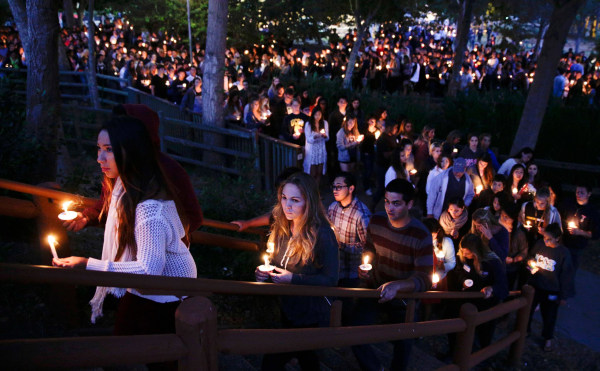 Image: People gather at a park for a candlelight vigil to honor the victims of Friday night's mass shooting on Saturday